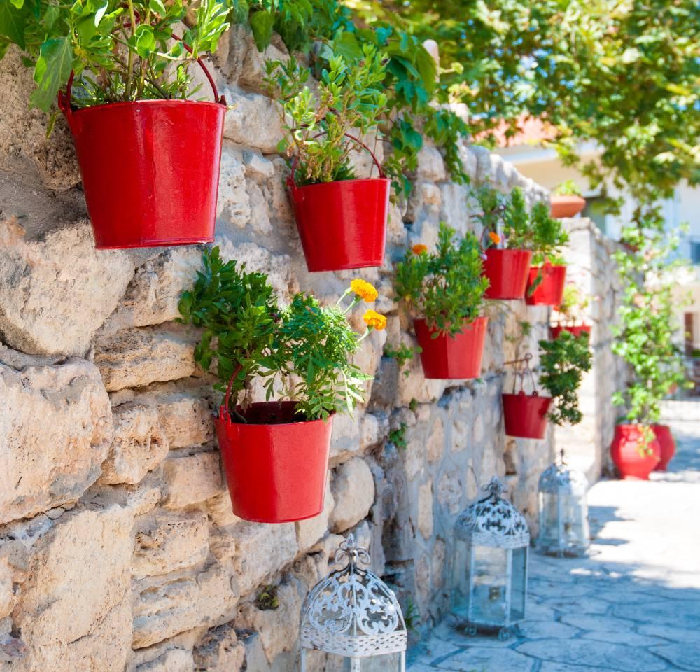 Osłonki na doniczki wiszące na starym murze