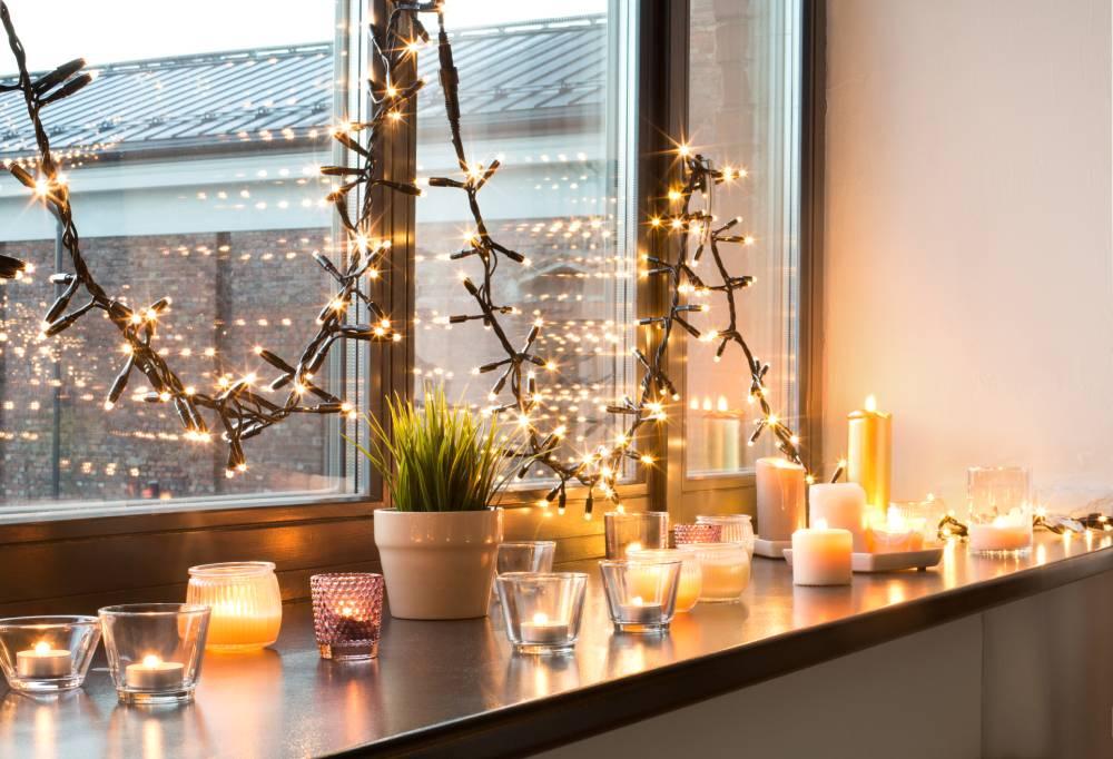 Świece i lampki zdobiące okno